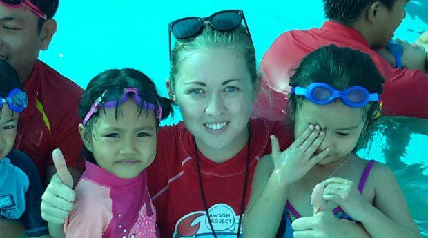 Emily McNeill helping kids learn to swim in Vietnam